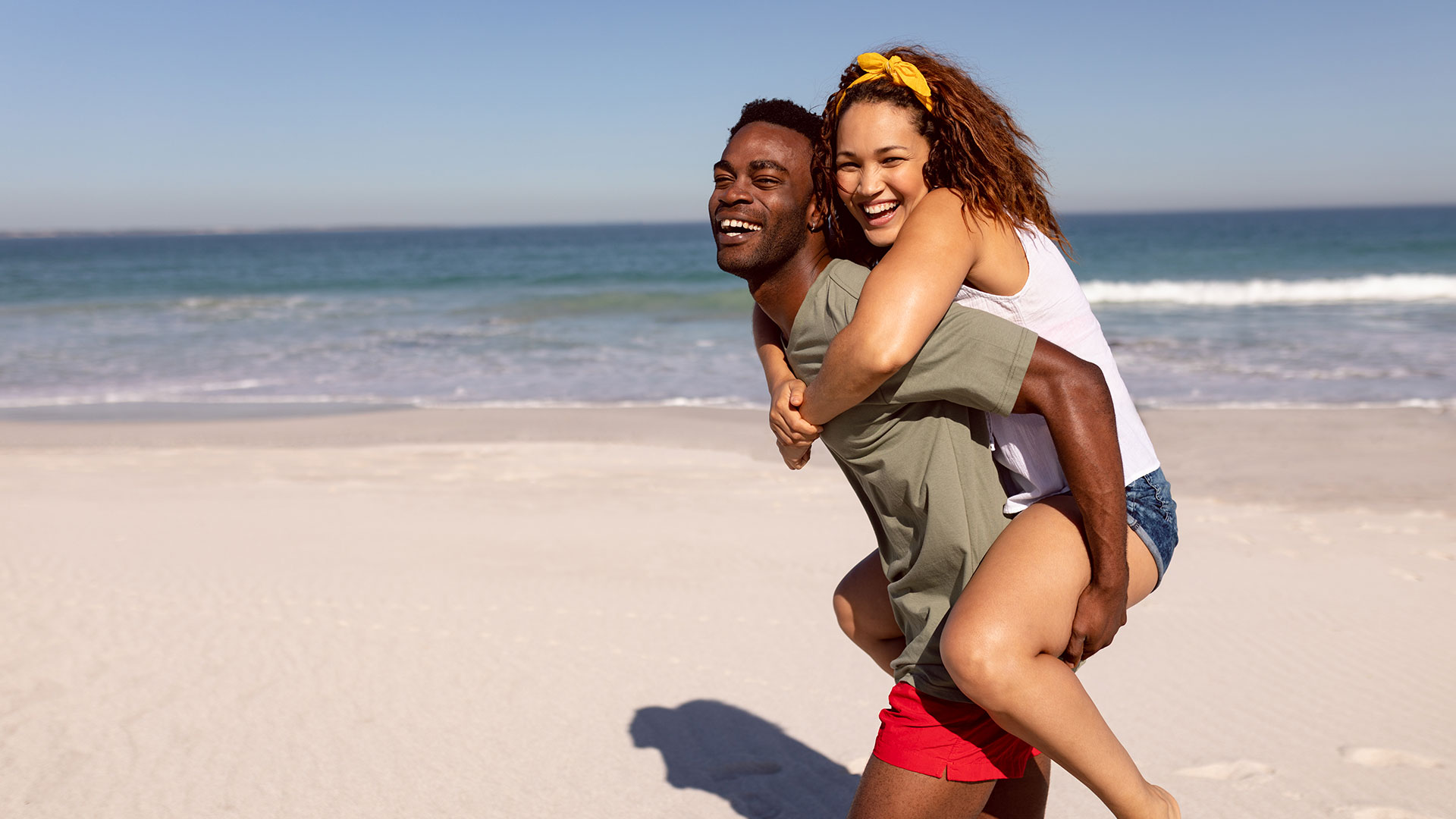 Man giving piggyback ride to woman on a beach in the sunshine.