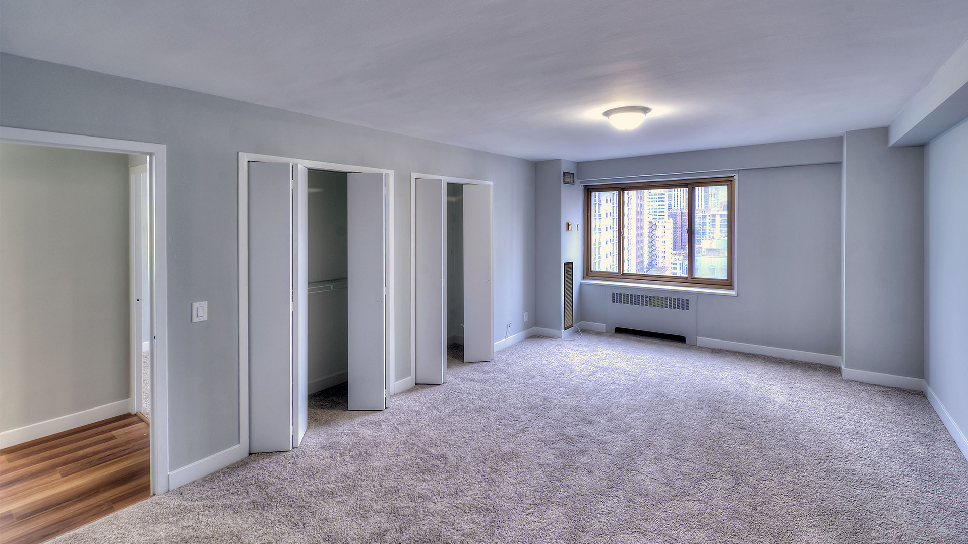 An empty bedroom in a 1350-1360 Lake Shore Drive residence with two large closets on the left wall and a view of Chicago out the window on the far wall.
