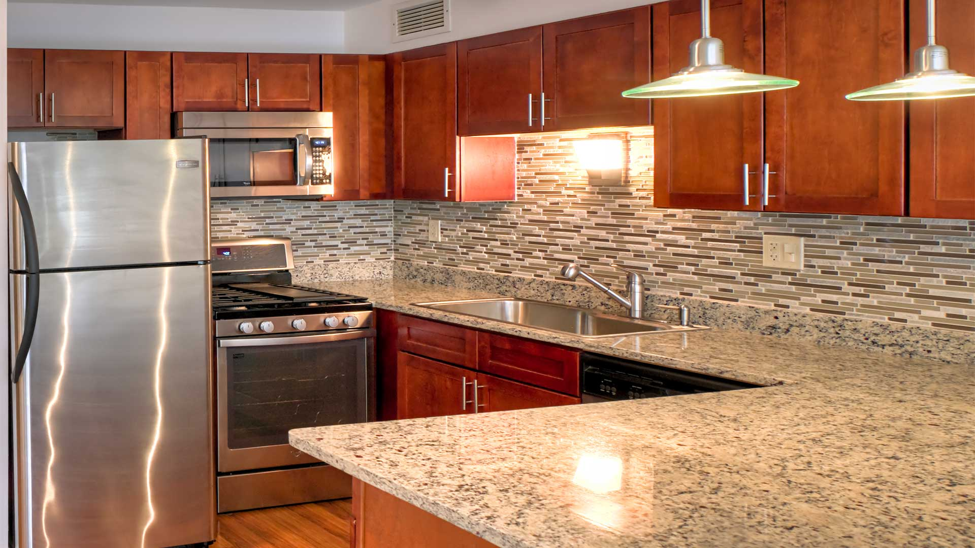 An updated kitchen in a 1350-1360 Lake Shore Drive residence. Stainless steel appliance line the back wall and the granite countertop wraps around to the right.