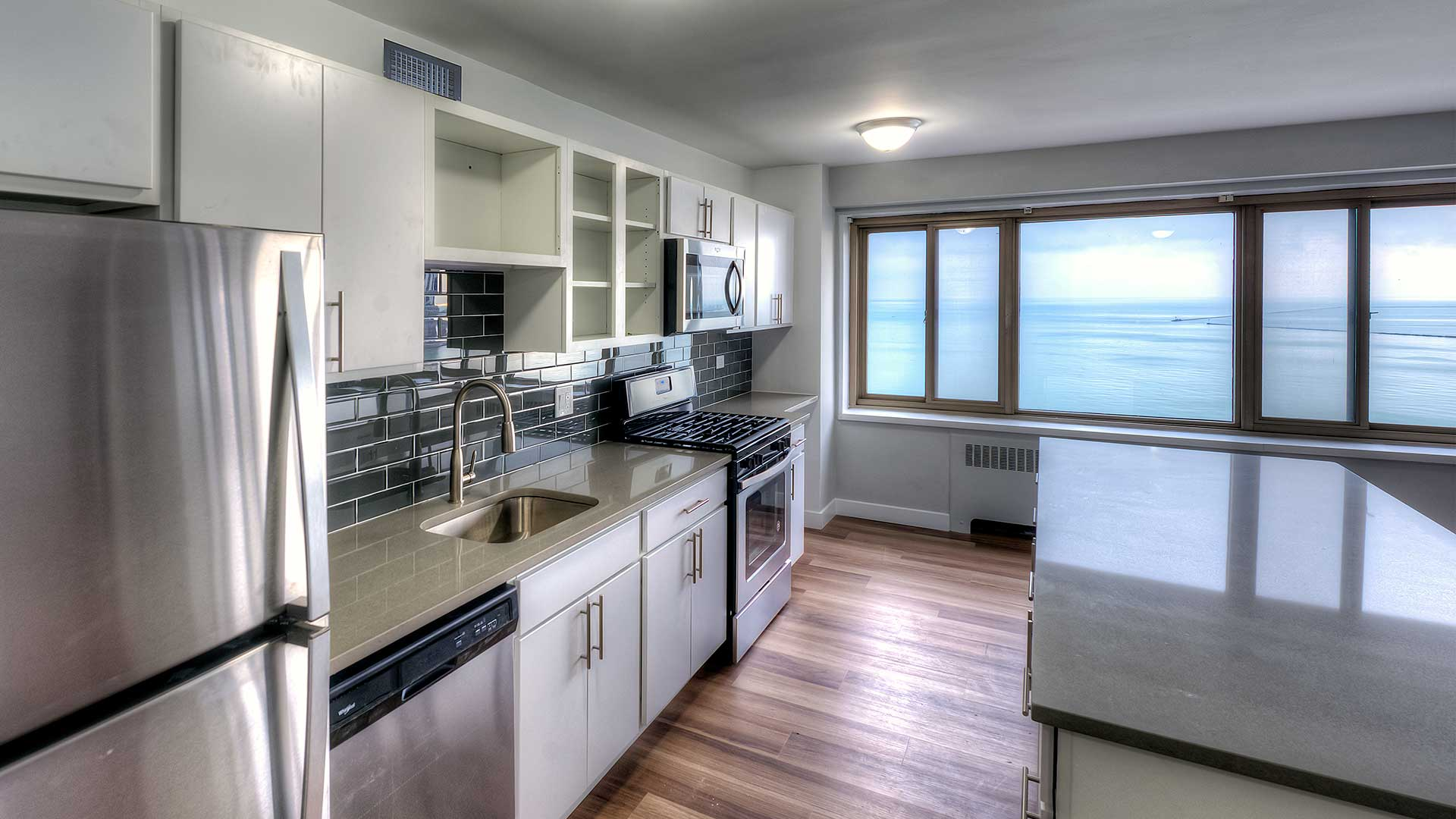 Standing at one end of residence kitchen, the stainless steel appliances and cabinets along the left and a kitchen island on the right. Lake Michigan is seen out the window on the far side of the room.