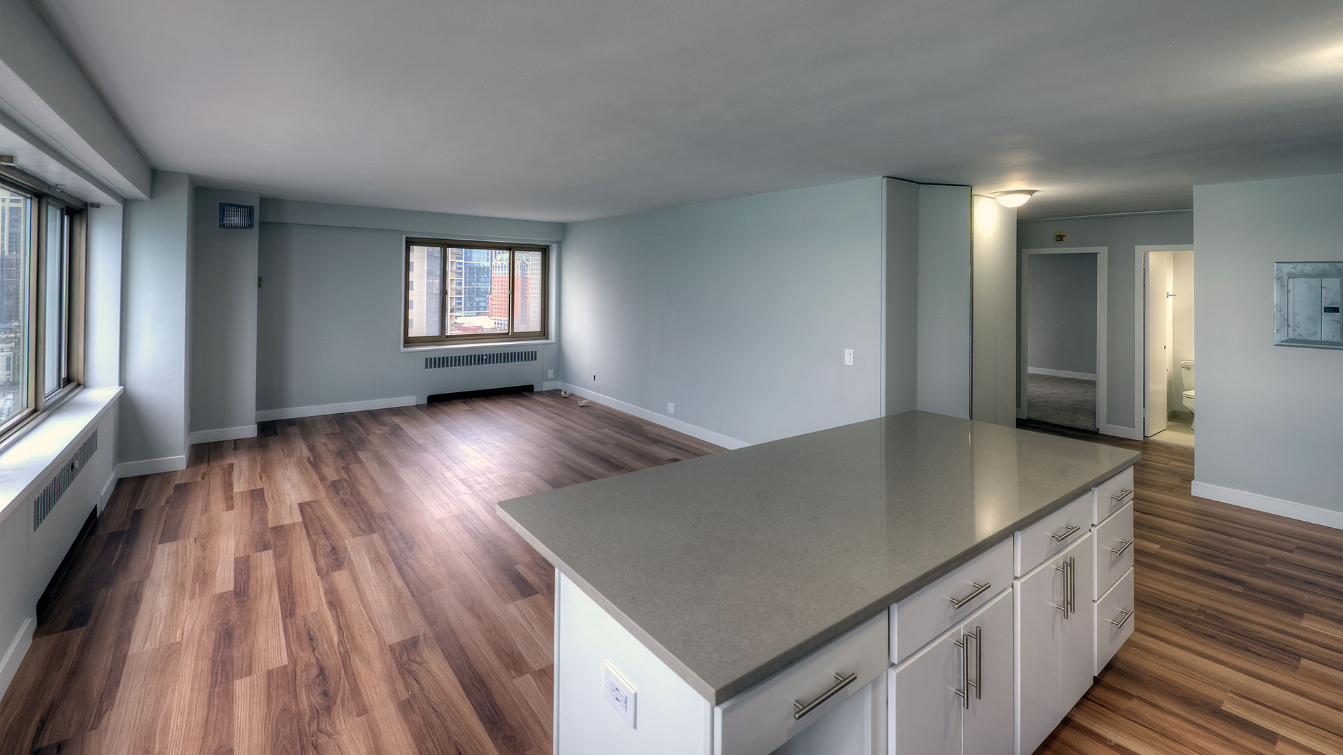 Looking out into an empty living room in a residence at 1350-1360 Lake Shore Drive. There is a kitchen island in the foreground and a short hallway off to the right.