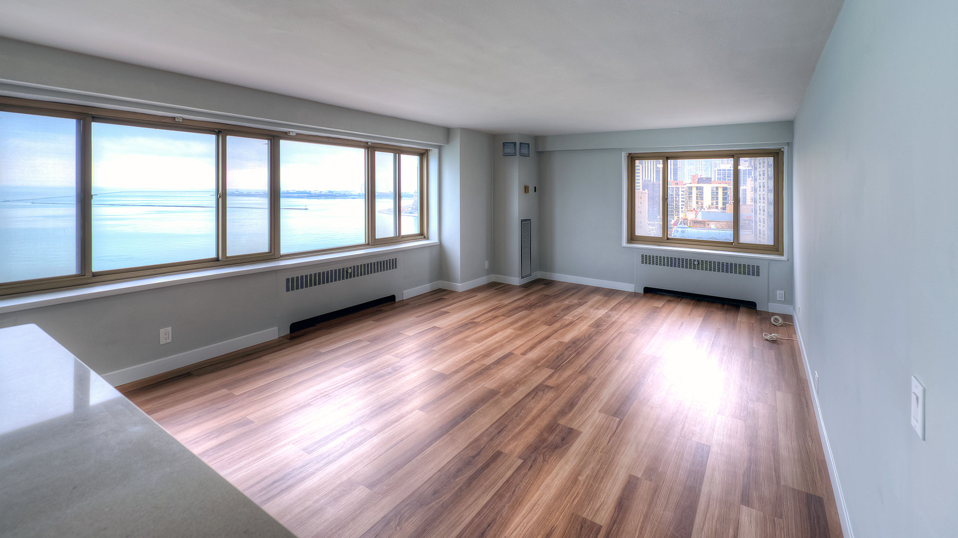 An empty living room of a 1350-1360 Lake Shore Drive residence. The windows on the left show Lake Michigan. The windows on the far side show the city of Chicago.