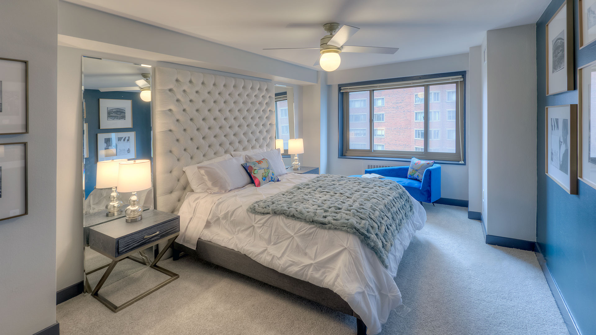 A bedroom in a residence at 1350-1360 Lake Shore Drive. A large bed with headboard to the ceiling is on the left wall with end tables and lit lamps on both sides. A lounge chair sits below the window on the far side of the room.